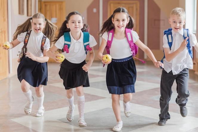 Niños con manzanas corriendo en el pasillo de la escuela