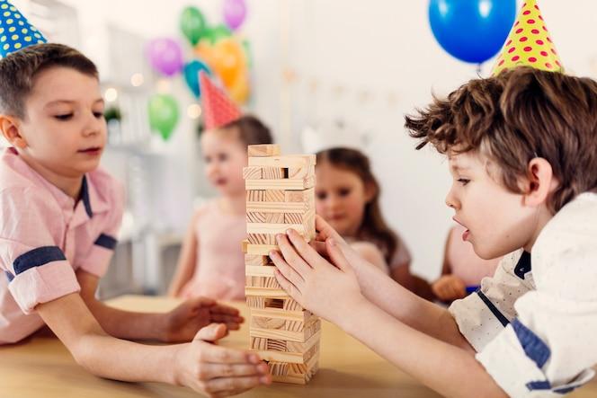 Niños concentrados con gorras de colores jugando al juego
