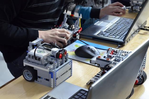 Los niños construyendo robots cerca del edificio del niño desde la educación de la creatividad de programación del constructor