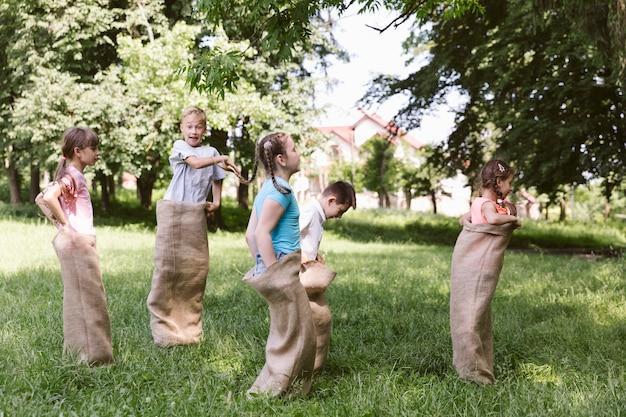 Niños corriendo en bolsas de arpillera.