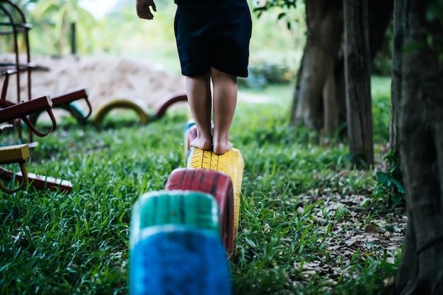 Niños corriendo con neumáticos en el patio de recreo.