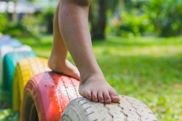 Niños corriendo con neumáticos en el patio de recreo