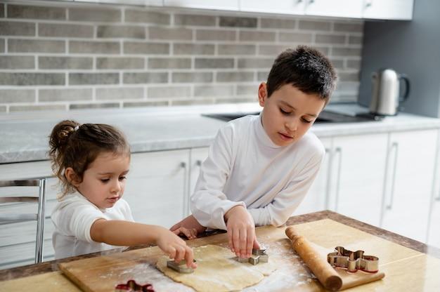 Los niños cortan galletas de la masa.