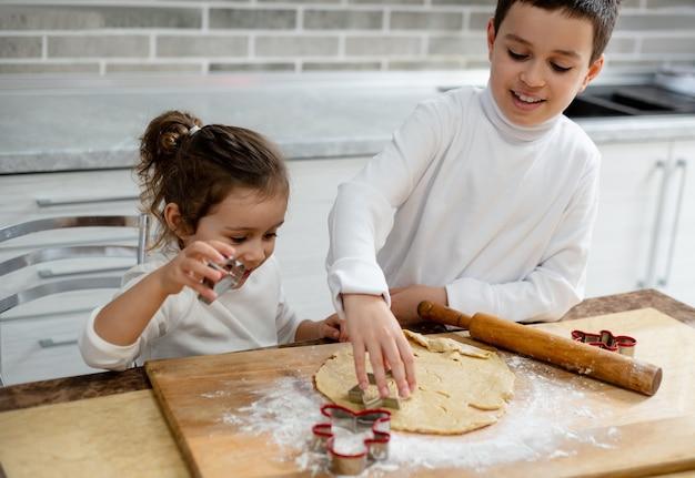Los niños cortarán las galletas navideñas con las formas especiales.