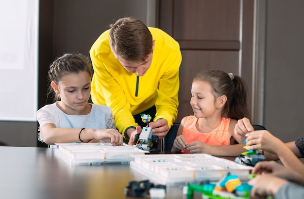 Niños creando robots con el maestro. desarrollo temprano, bricolaje, innovación, tecnología moderna.