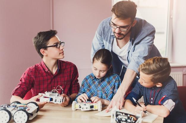 Niños creando robots con profesor