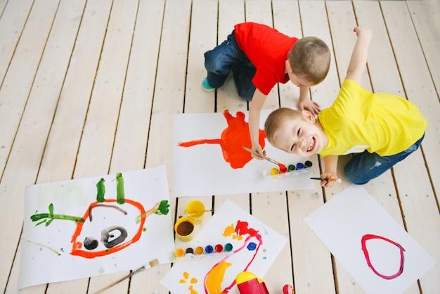 Los niños creativos pintan con pincel sobre papel divertidas imágenes coloridas en un piso