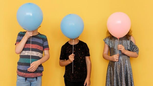Niños cubriendo caras con globos.