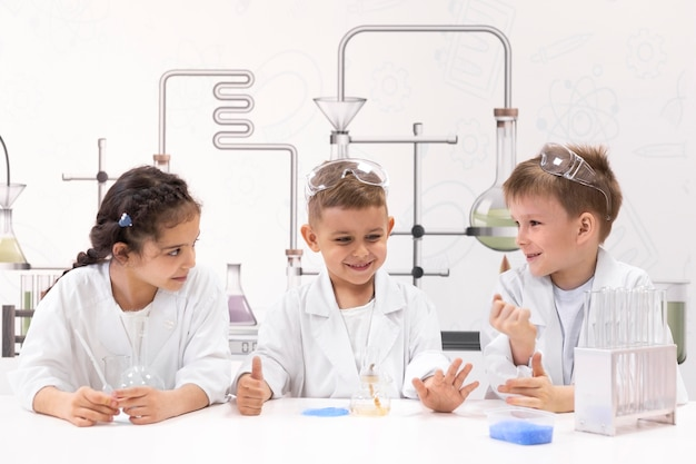 Niños curiosos haciendo un experimento químico en la escuela.