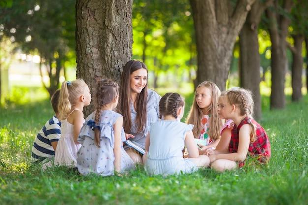 Los niños dan una lección con el maestro en el parque sobre un césped verde.
