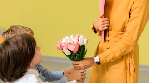 Niños dando a su maestra un ramo de flores.