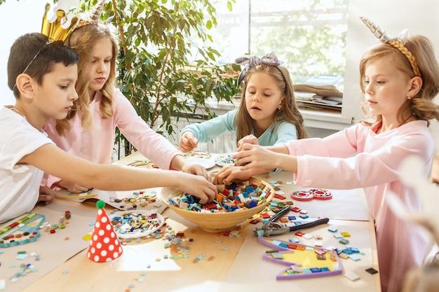 Los niños y las decoraciones de cumpleaños. los niños y niñas en la mesa con comida, pasteles, bebidas y artículos de fiesta.
