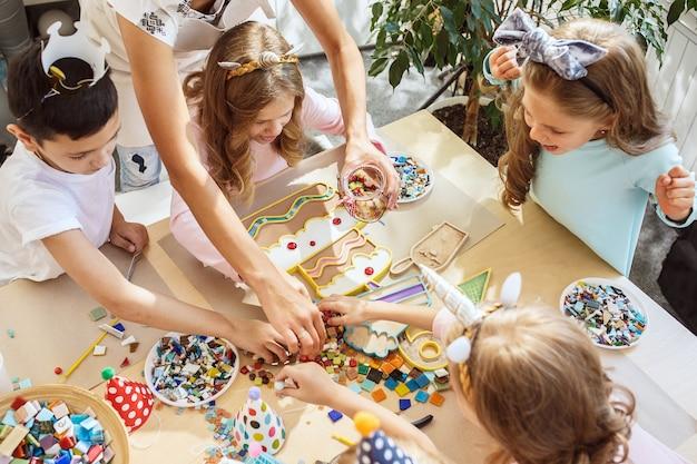 Niños y decoraciones de cumpleaños. niños y niñas en la mesa con comida, pasteles, bebidas y artículos de fiesta.