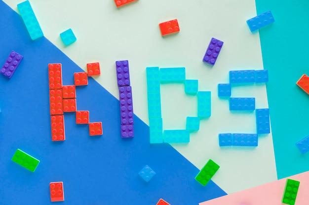 Los niños deletrean palabra con fondo de bloques de plástico