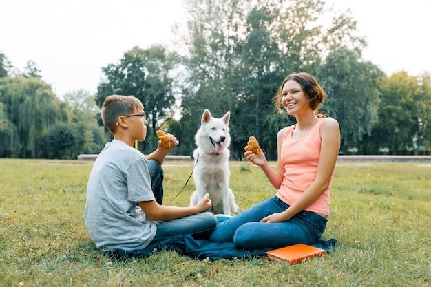 Los niños descansan en el parque sobre césped verde con un perro blanco husky, comen cruasanes, hablan