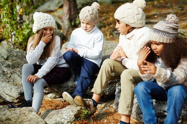 Niños descansando en el soleado bosque de otoño