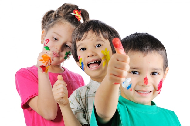 Niños desordenados con pintura en sus manos y caras con los pulgares arriba