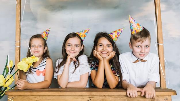Niños detrás de la parada en la fiesta de cumpleaños