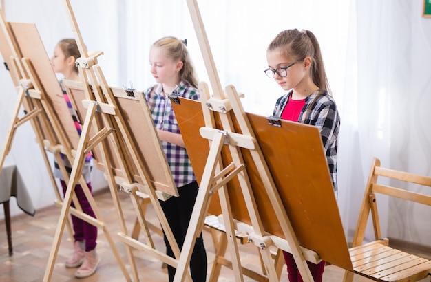Los niños dibujan en un caballete en la escuela de arte.
