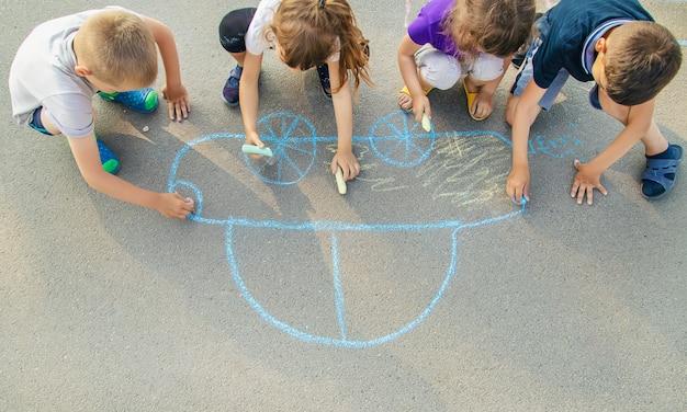 Niños dibujan un coche con tiza en el pavimento.