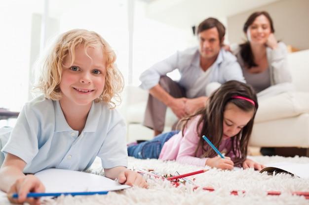 Los niños dibujan mientras sus padres están en el fondo