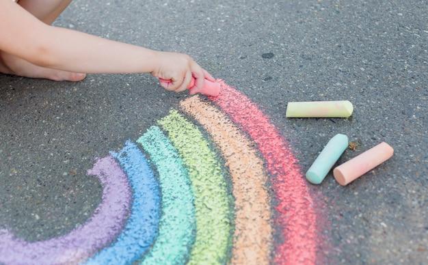 Niños dibujando arcoiris con tiza de colores sobre pavimento