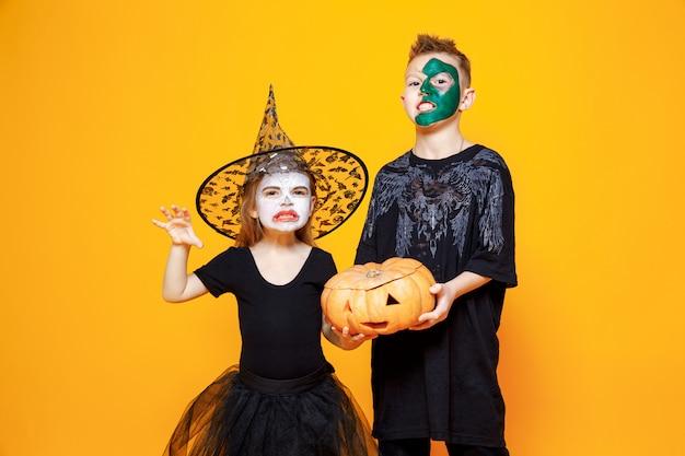 Niños en disfraces de halloween sosteniendo una calabaza