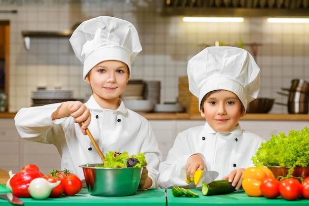 Niños disfrazados de cocinero en la cocina