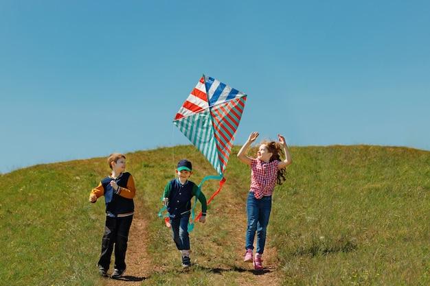 Los niños disfrutan jugando con una cometa voladora.
