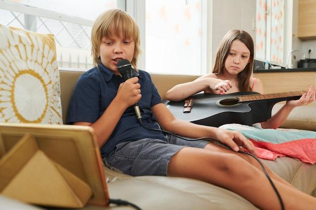 Niños disfrutando de karaoke en casa.