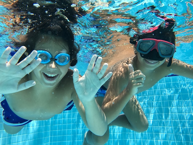 Niños disfrutando en la piscina bajo el agua