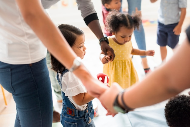 Niños diversos jóvenes parados con sus padres.