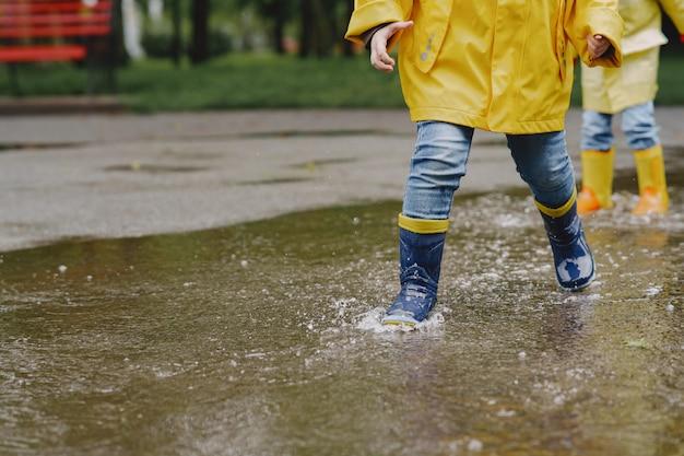 Niños divertidos en botas de lluvia jugando con barco de papel por un charco