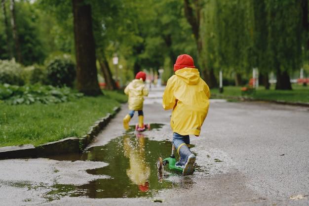 Niños divertidos con botas de lluvia jugando con patines