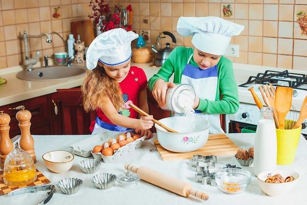 Niños divertidos de la familia feliz están preparando la masa, hornear galletas en la cocina