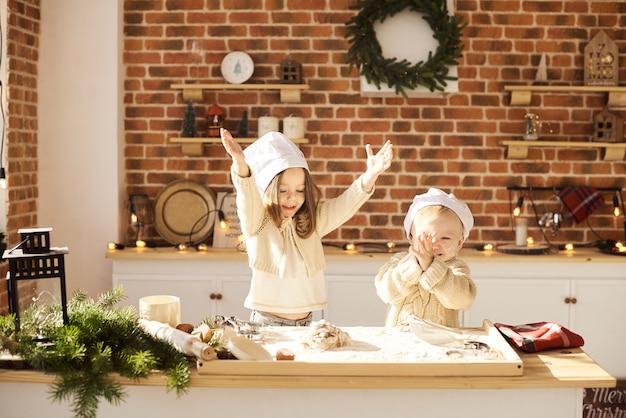 Los niños divertidos de la familia feliz están preparando la masa, jugando con la harina en la cocina.