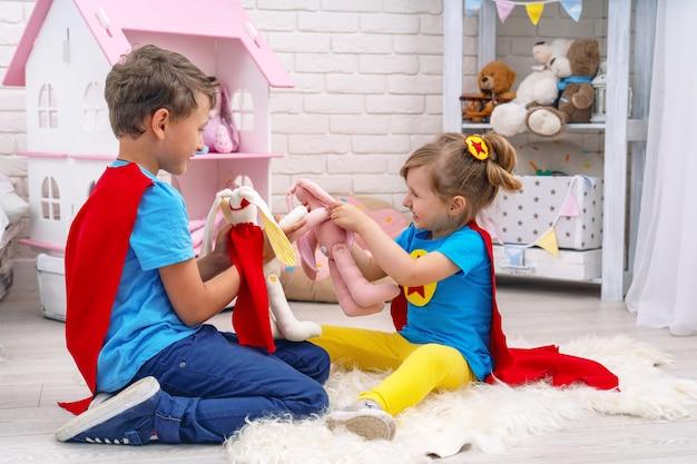 Niños divertidos juegan con juguetes en los superhéroes, en la habitación de los niños