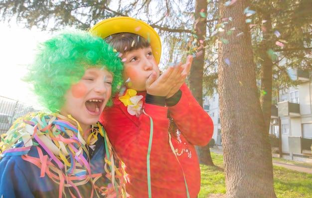 Niños divertidos niñas celebran el carnaval sonriendo y divirtiéndose con confeti de colores