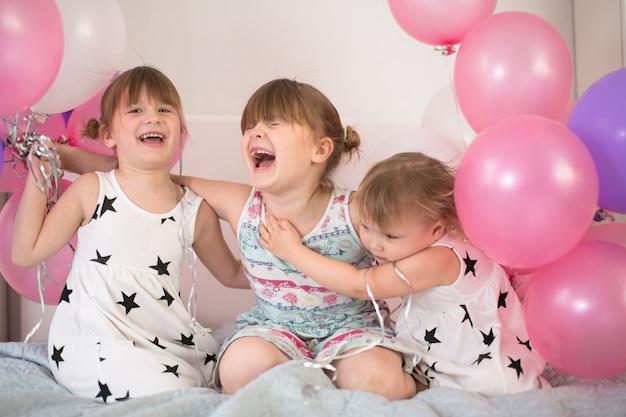 Niños divertidos niñas en vestidos con globos