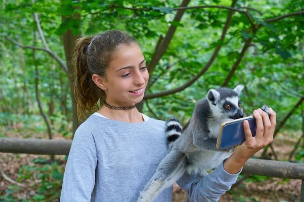 Niños divirtiéndose con animales de lémures de cola anillada.