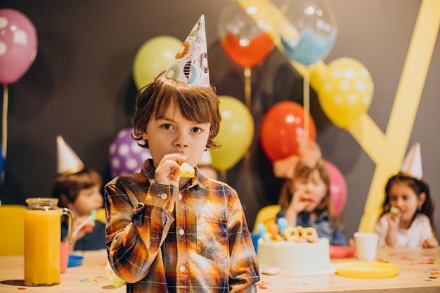 Niños divirtiéndose en la fiesta de cumpleaños con globos y pastel.