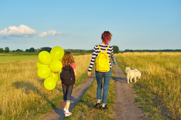 Niños dos niñas caminando por el camino rural con perro y globo, vista posterior
