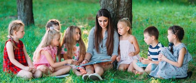 Niños y educación, joven en el trabajo como educadora leyendo libros para niños y niñas en el parque.