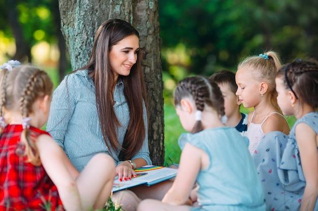 Niños y educación, mujer joven en el trabajo como educadora leyendo un libro a niños y niñas en el parque