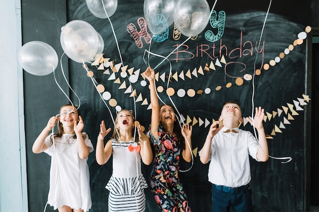 Niños emocionados soltando globos en la fiesta