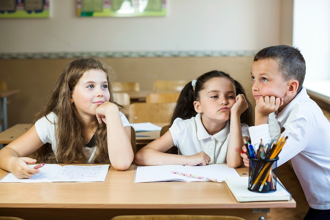 Niños en el escritorio con los libros de texto