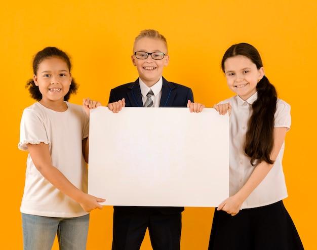 Niños encantadores sosteniendo pancarta en blanco