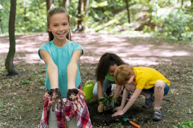 Los niños se ensucian las manos después de plantar