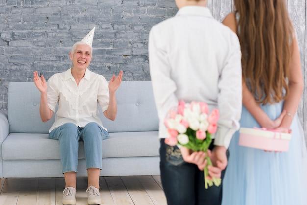 Niños escondiendo regalos detrás de su espalda de pie frente a su abuela