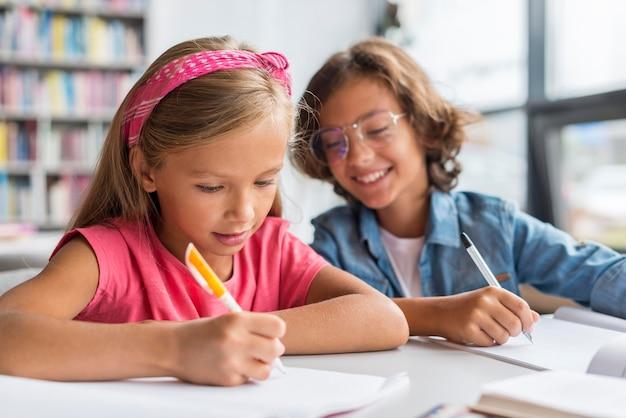 Niños escribiendo sus deberes en la biblioteca.